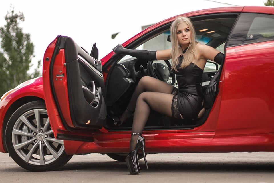 Девушка в короткой юбке на каблуках возле машины