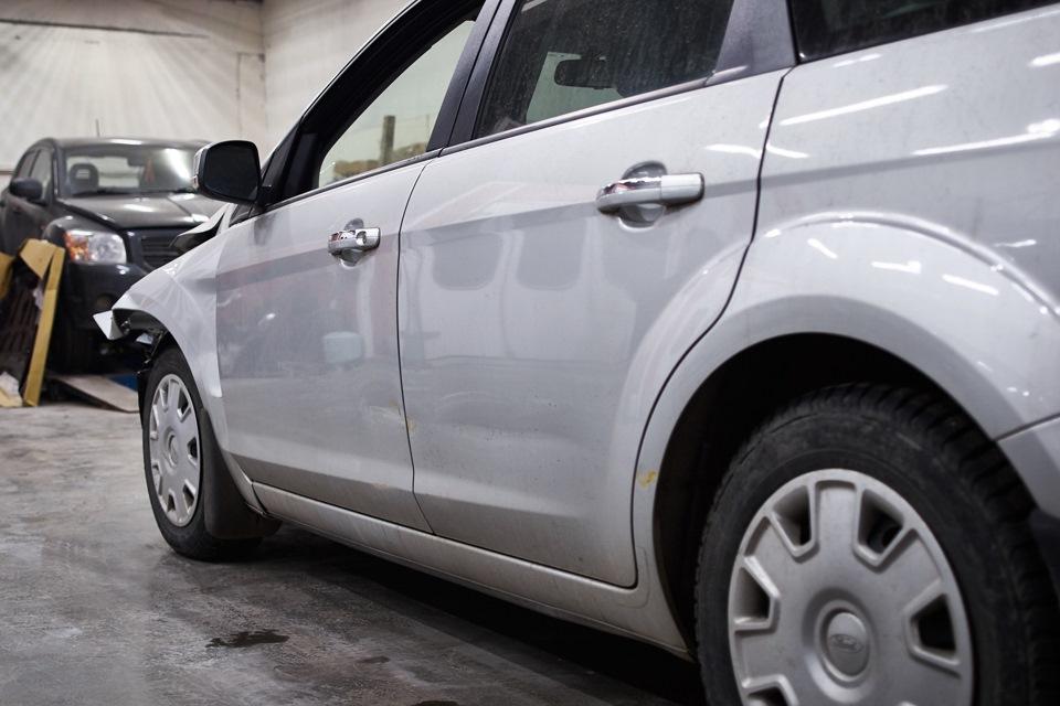Повреждения кузовных элементов Ford Focus с левой стороны. Видна полоска вмятины на обеих дверях и заднем крыле.