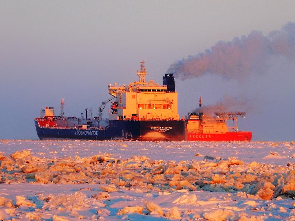 Справа от танкера «Штурман Альбанов» видно многофункциональное аварийно-спасательное судно «Балтика». Очень необычное судно, потому что имеет ассиметричный корпус – один борт прямой, а другой выпуклый. «Балтика» может двигаться и колоть лёд до метра толщиной не только передом или задом, но и боком. Тем самым может делать канал до 50 метров шириной. Для справки, самый большой в мире ледокол «50 лет Победы» делает канал всего 30 метров, а ширина танкеров доходит до 45 метров.