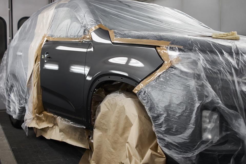 Свежеокрашенные поверхности переднего правого крыла и передней правой двери KIA Sorento перед окончательной сушкой в покрасочной камере