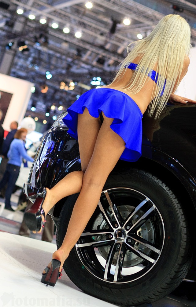 Большими девушка в коротком платье наклоняется к машине дома смотреть