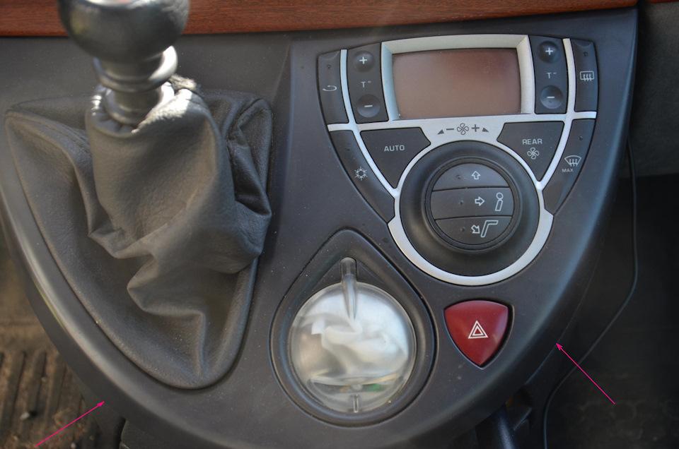 • На фото видна панель, под которой расположен сам блок климат-контроля (КК), кнопка «аварийки» и в эту же панель встроен небольшой отсек для мелочей (некоторые его называют пепельницей, но это не так). В местах, куда указывают стрелки, нужно надавить снизу вверх, как бы открыть крышку.
