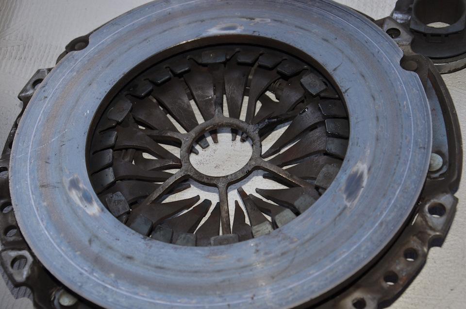 Старая корзина, сторона прилегающая к диску сцепления. Видны три потертости. Вероятно из-за биений сломанного маховика и произошел данный дефект.
