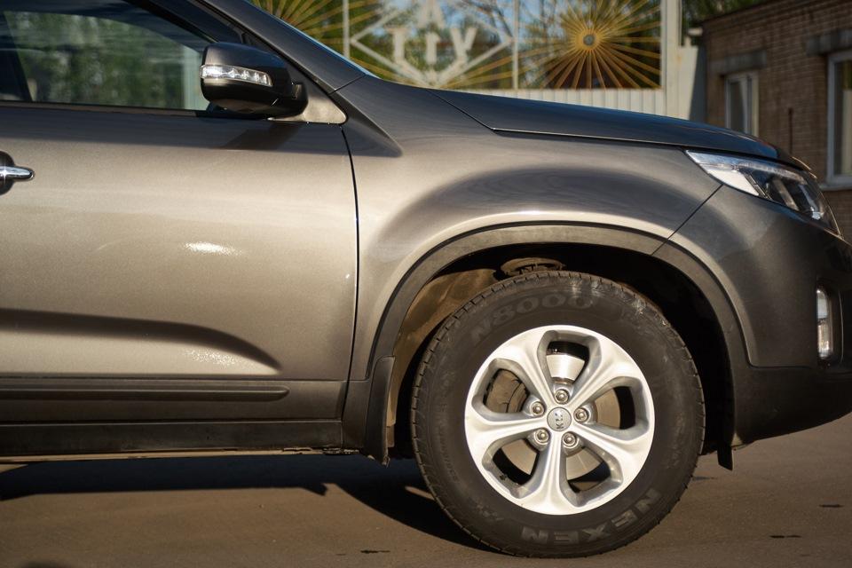 Внешний вид кузовных элементов KIA Sorento после проведённого ремонта и локальной покраски с переходом. Фото при ярком закатном солнечном свете